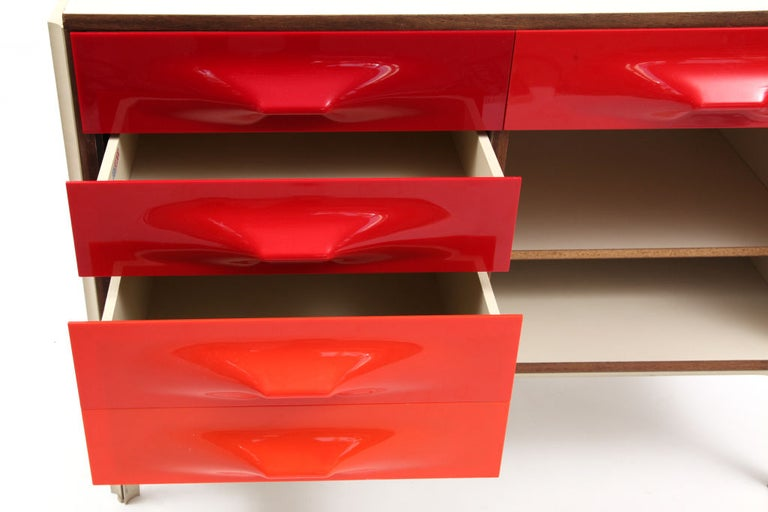 Raymond Loewy for Doubinsky Freres chest of drawers circa mid-1960s. This example has the iconic orange and red pop drawer fronts, sliding top with interior storage and rosewood trim. The sliding top can also be used as a desk, making this piece