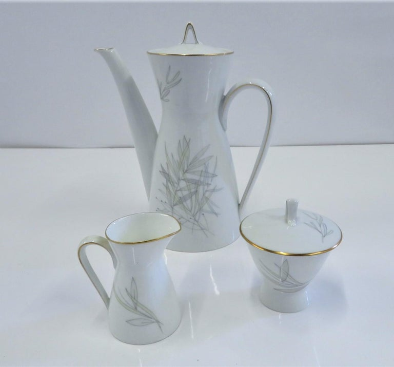 """A Mid-Century Modern porcelain coffee service set consisting of coffee pot, creamer and lidded sugar byRosenthalin theGRASSESpattern with the iconic """"2000"""" form designed byRaymond Loewy in the 1950s. This lovely pattern is decorated with gray,"""
