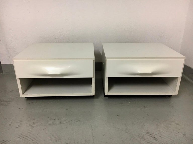 Pair of bedsude tables, white laminate wood cabinet with white moulded plastic frond drawer By Raymond Loewy produced by Doubinsky Frères DF2000, France circa 1960s Good vintage condition.