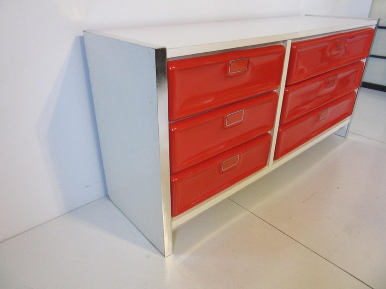 A very 1970s six drawer pop dresser with molded plastic fronts , flip metal handles , aluminum edged and white Formica cabinet . In the manner of Raymond Lowey and Broyhill furniture .