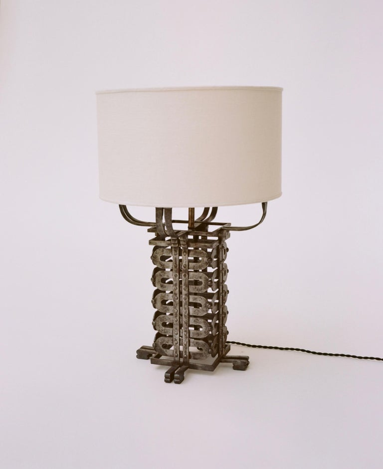 A silver-gilt wrought iron table lamp with cream colored linen shade. Rewired for US outlets and fitted with a custom ivory silk linen shade and cord. Exemplary of the more elaborate, art deco period with far eastern influences. Measurements with
