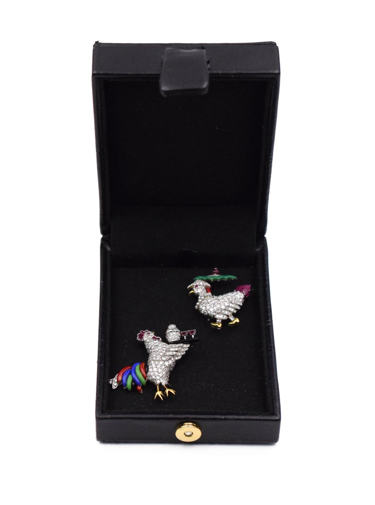 Ruby and Enamel Rooster Pin, Raymond Yard The rooster fashioned as a stylized cocktail waiter pavé-set with single- cut diamonds, holding a black enamel tray with shaker and martini glasses, signed Yard. Measurements: 1 1/2 inches and 1 1/2