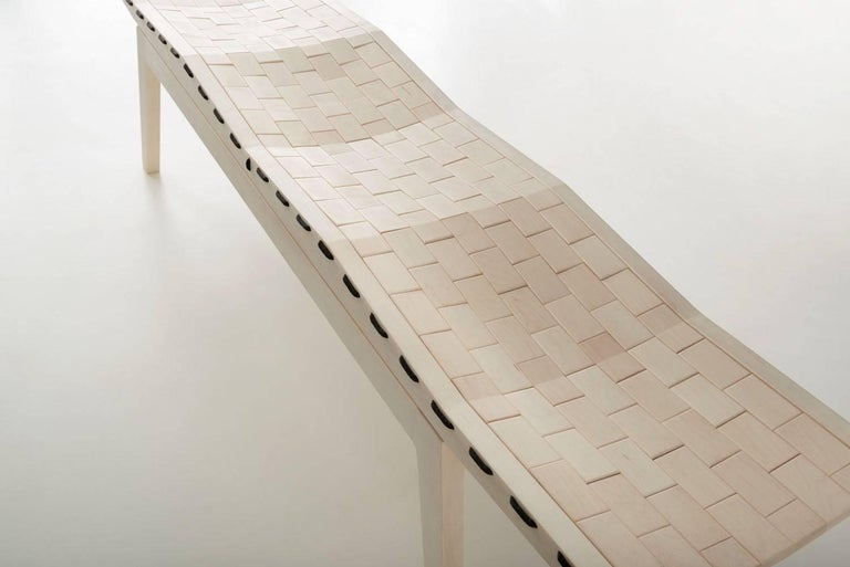 Woodsport RB bench. Named after the running bond pattern in which bricks are laid. Individual pieces of bleached maple are laced together with high grade polyester rope, creating a flexible surface that forms to the occupant. The bench is detailed