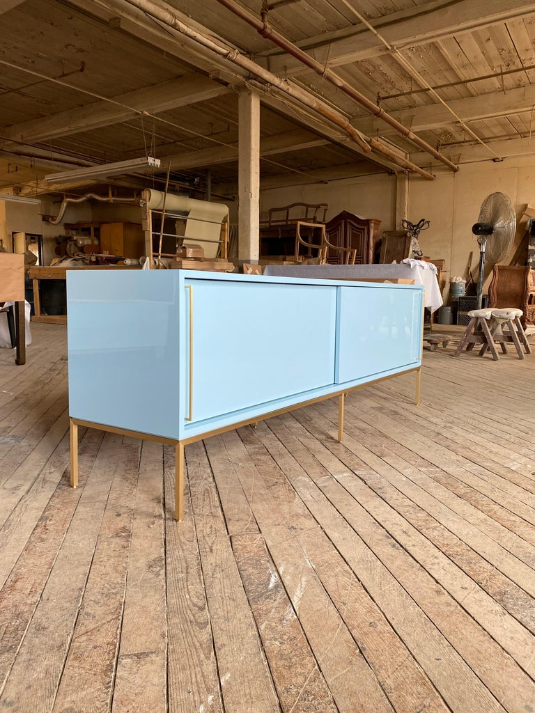 reGeneration has become known for this iconic credenza which is so versatile, clients order them again and again. It is shown here in Benjamin Moore, Marlborough blue on a handcrafted satin brass base. Sliding doors conceal two adjustable interior