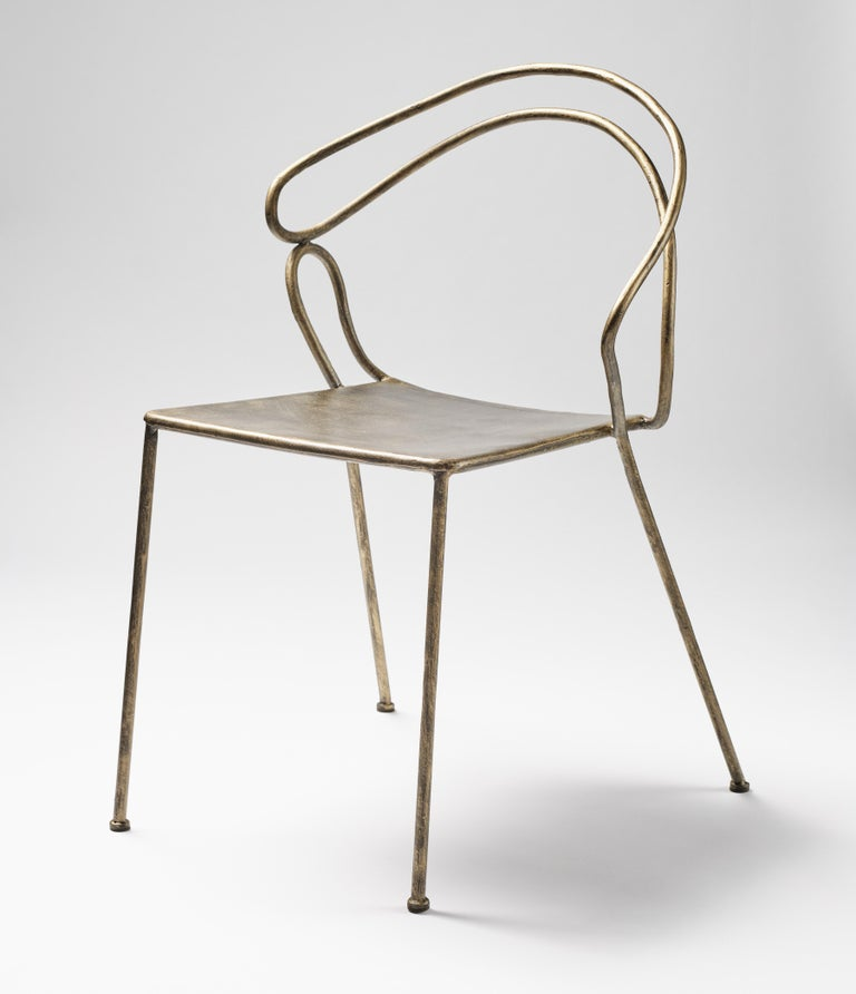 A unique and metaphysical chair, from a design that sinks into the archeology of the mind in a contemporary key. From the soft and sinuous line, the back and the rear legs form a sculptural unicum forged and shaped by hand. The seat, also