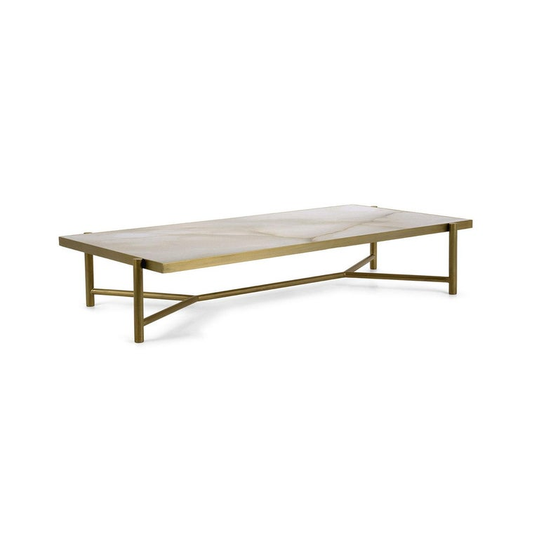 Refined in its rigorous simplicity, this glamorous coffee table is part of a collection inspired by Rhea, Titaness and mother of Zeus in Greek mythology. The dynamic metal structure with a burnished brass finish comprises the legs sustaining the