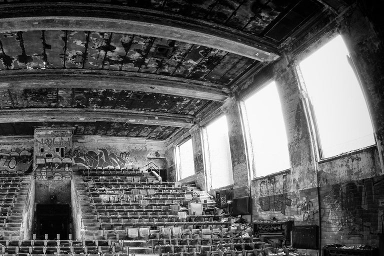 "Rebecca Skinner's ""Burned Out"" is a 24 x 36 inch black and white metal print of a theater in an abandoned school. With satin finish, the image is infused directly into metal making it waterproof and easy to clean. This frameless metal print hangs"