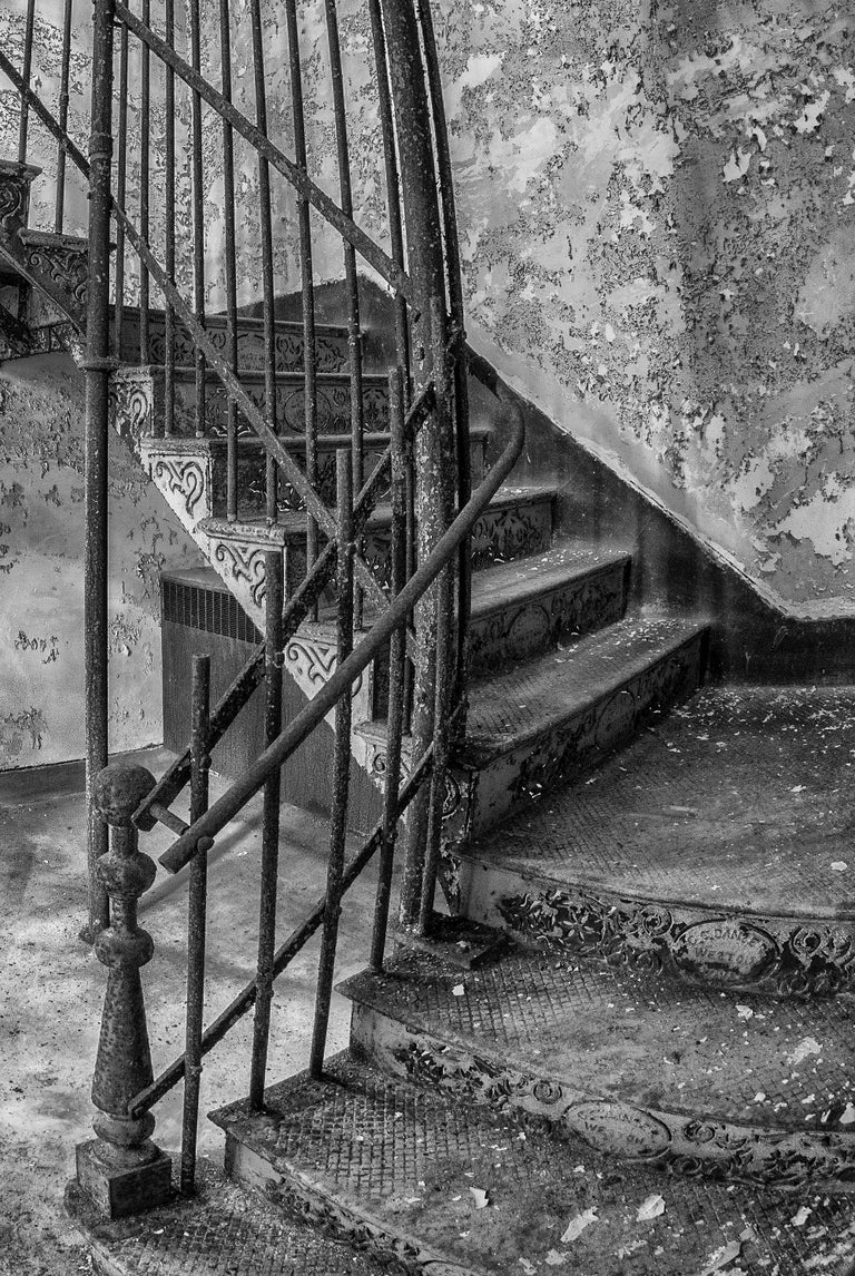 """Rebecca Skinner's """"Stairway"""" was photographed at an abandoned asylum and is part of her """"Forgotten"""" series raising mental health awareness. A fisheye lens gives the ornate, iron staircase a never ending feeling. Patterned cutouts in the steel risers"""