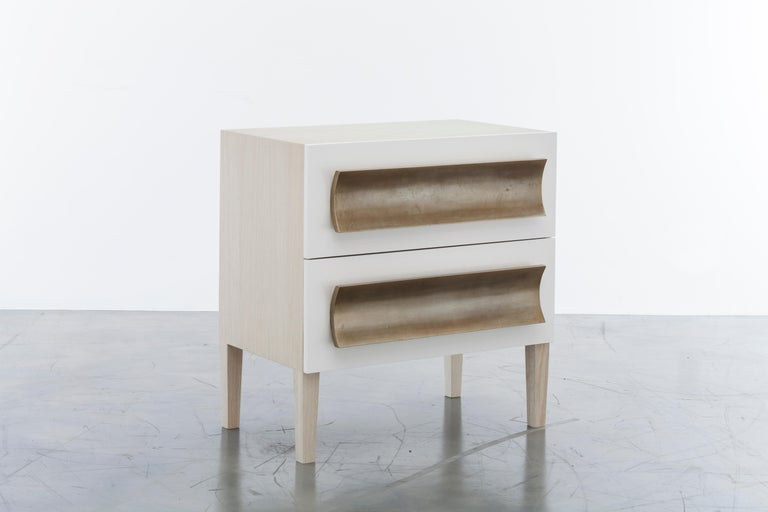 The Recaimer nightstand features a unique mixed finish design with an oak body, lacquer drawer fronts and antique silver leaf hand-carved pull details. Drawers are standard soft close with hidden glides. Fully custom and made to order in California.