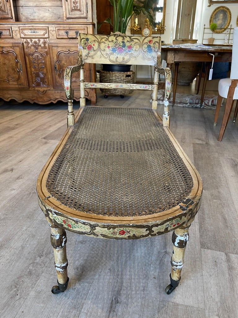Delightful paint decorated and caned recamier, circa 1830, likely Regency, the curved tablet form crest rail atop thin horizontal splat flanked by scrolled open arms all surmounting elongated bow front frame inset with caning raised on six legs
