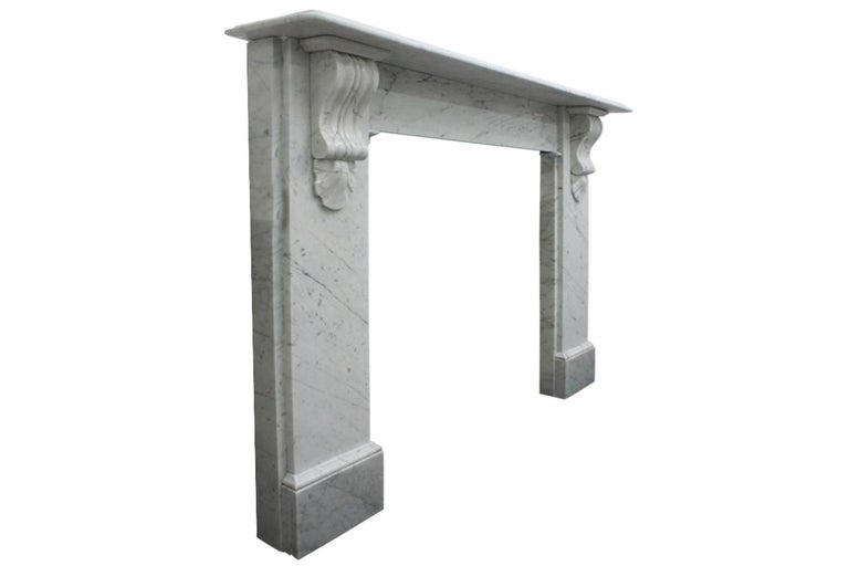 Reclaimed Victorian Carrara marble fireplace surround with classically carved corbels supporting the shelf, circa 1880.
