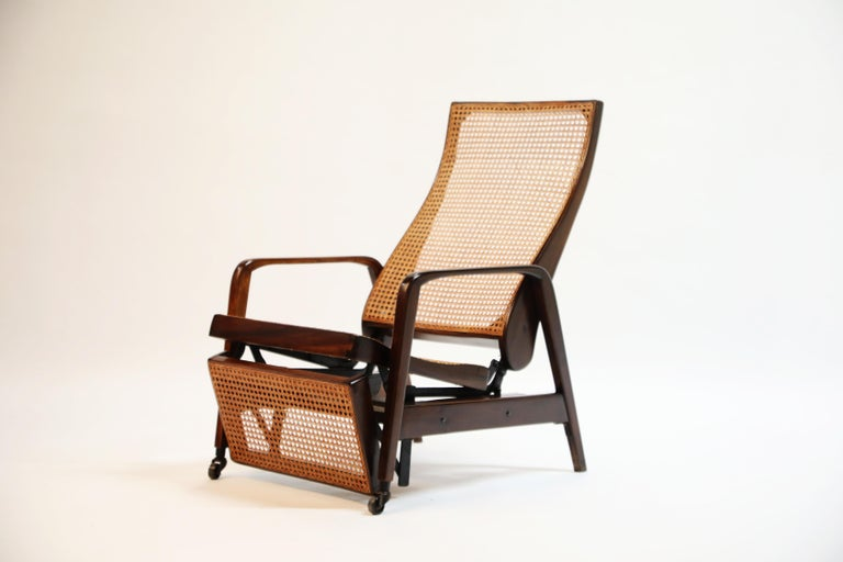 A beautiful caned reclining chair in Brazilian Jacaranda Rosewood made in Brazil circa 1940 with a sweeping curved seat back, sculptural arms and wheeled front legs. We recently imported this piece for Rio de Janeiro where we sourced this along with