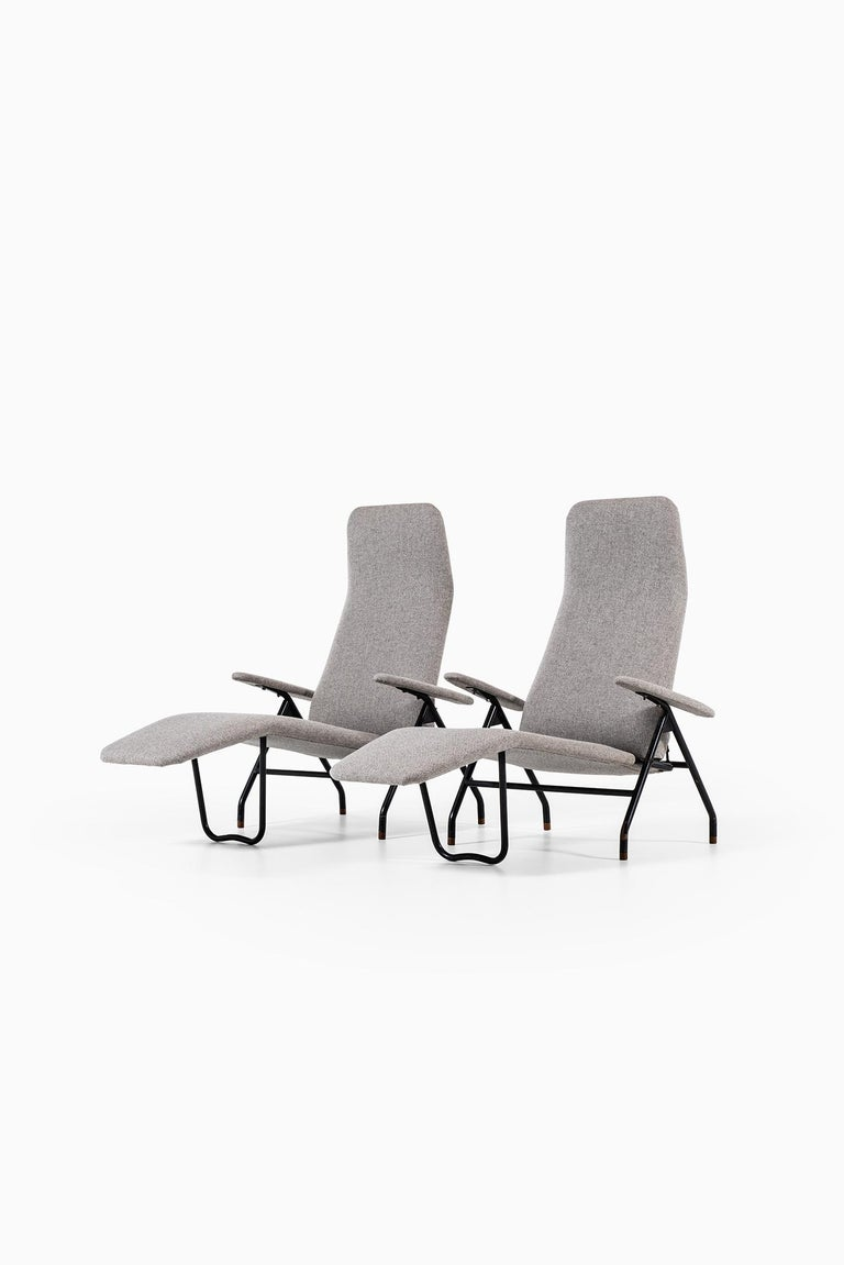 A pair of reclining easy chairs. Produced in Denmark. Black lacquered steel and newly reupholstered in grey fabric.