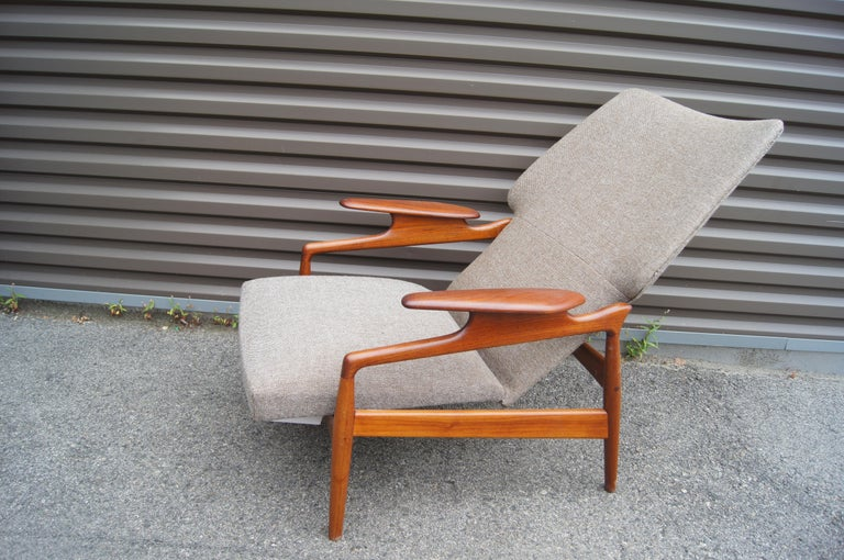 This 1960s teak lounge chair, by the Danish designer John Boné for Advance Design, adjusts from an upright to a reclining position. It features a gently curved wing-back profile and sculptural armrests. The chair has been refinished to bring out the