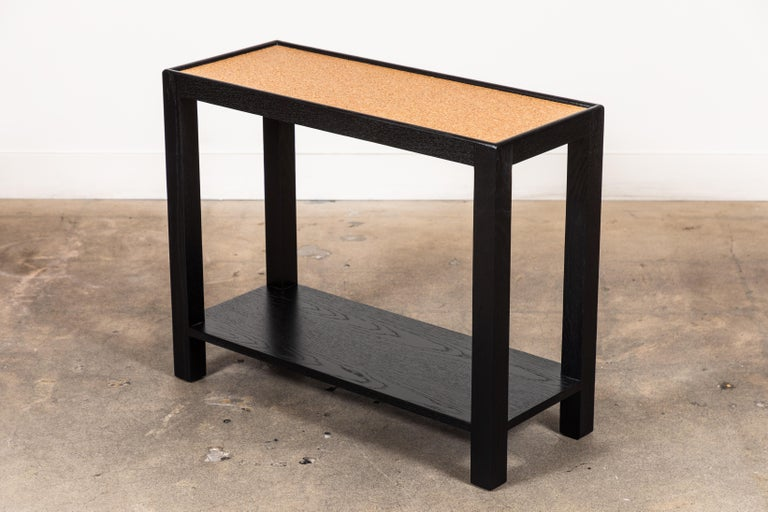 The Narrow side table is made of solid American walnut or white oak and features a lower shelf and your choice of a cork or bronze mirror top. Shown here in ebonized oak and natural cork.   Available to order in various finishes with a 10-12 week