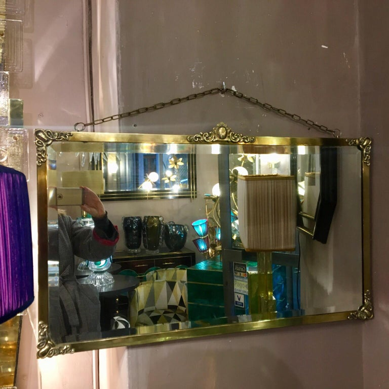 Rectangular Art Nouveau mirror with brass frame and brass friezes. Beveled original mirror, brass chain to hang the mirror.
