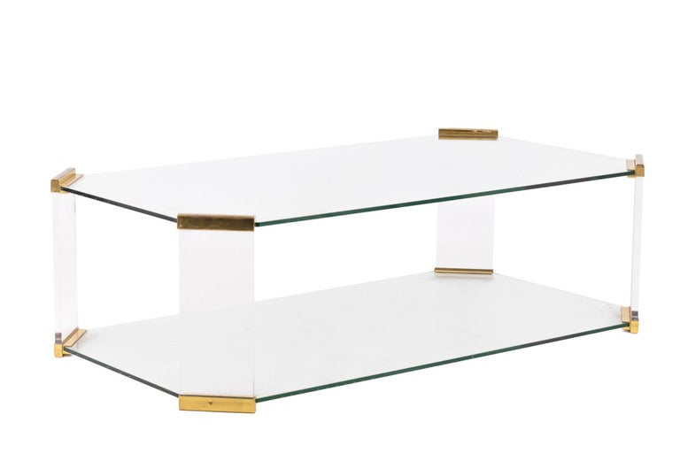 Rectangular glass coffee table with canted corners and stretcher glass tray. Gilt bronze joints on corners. Work from the 1970s.
