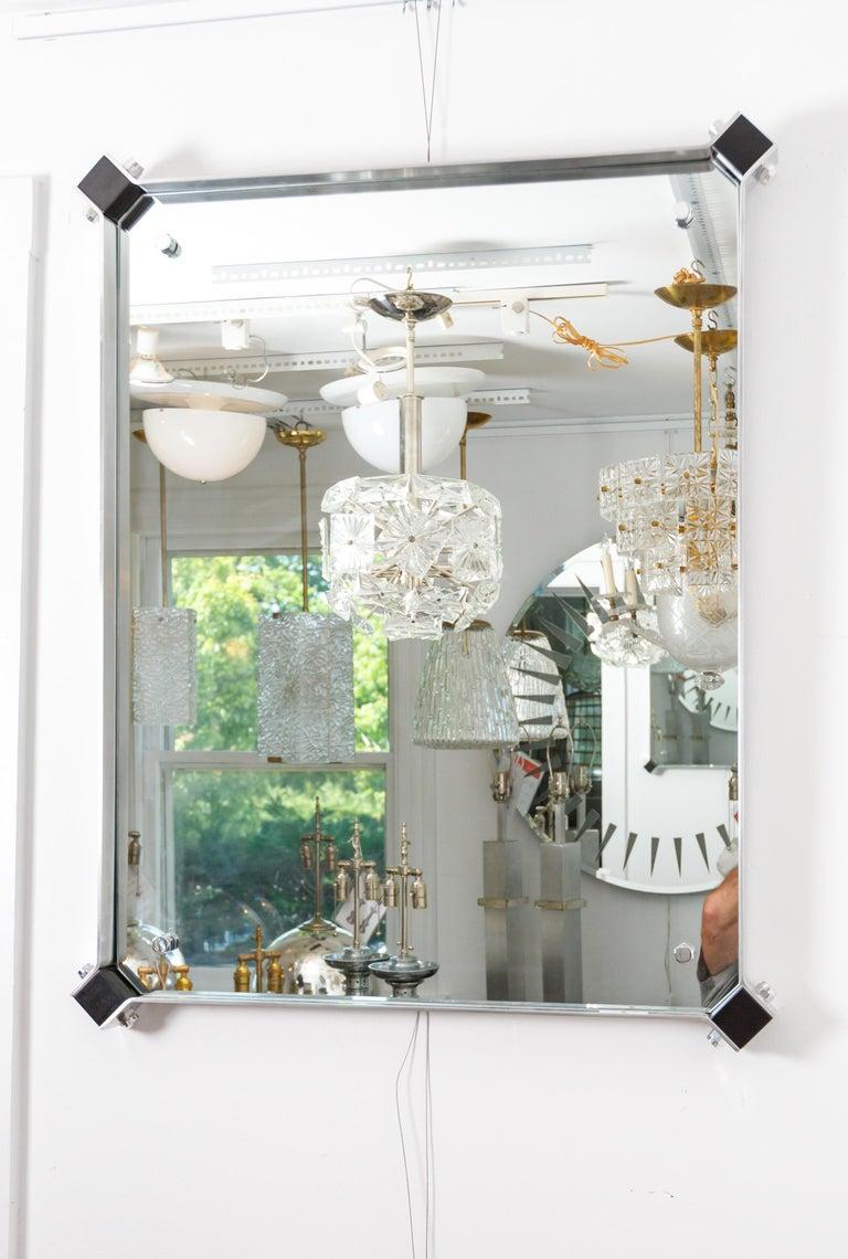 Rectangular mirror with stainless steel surround with black corner details.