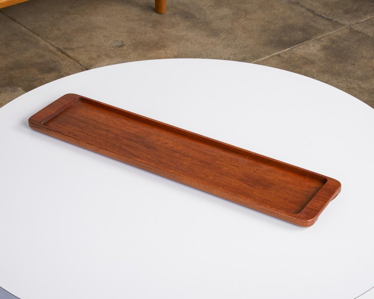 Rectangular teak serving tray by ESA Denmark, circa 1960s. The slender tray features raised edges with an inset middle section perfect for serving your favorite cheese and crackers. The narrow ends feature a cut out section underneath that is meant