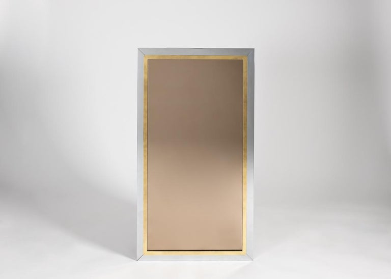 An elegant rectangular mirror with a frame of chrome complemented with a border of brass.
