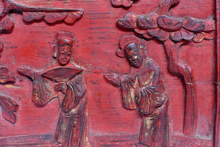 A red lacquered 19th century wood carving panel featuring two friends in their traditional official robes yielding the path for each other. Evergreen pine tree is symbolic of long lasting friendship. A partial peony hints prosperity. Hand carved.