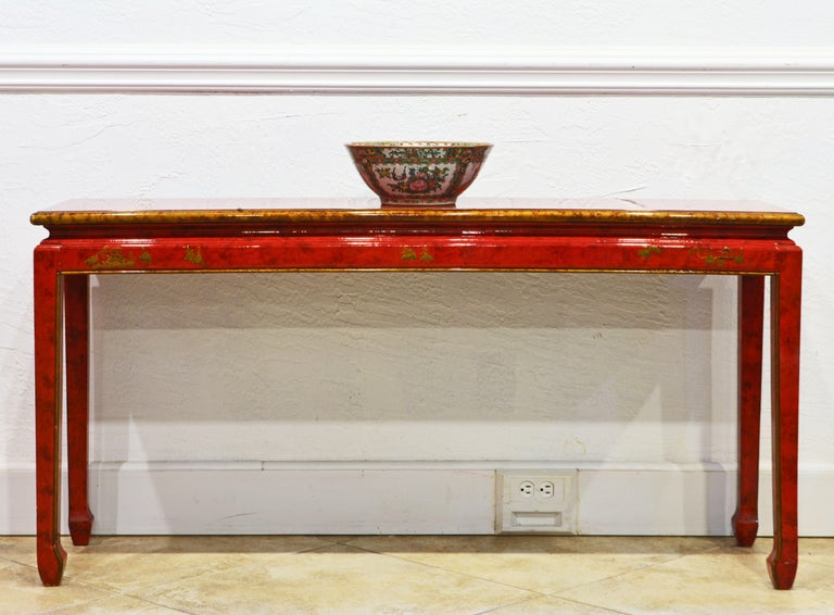 This elegant mid century lacquered chinoiserie Ming style console table features a waisted top decorated with gold finish bands and edge above the frame with chinoiserie gilt motifs and four Ming style legs accented by gold finished edges. The table