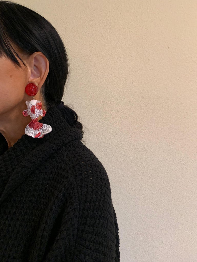Light and easy to wear, these contemporary handmade artisanal clip-on earrings were made in Paris by Cilea. The lightweight statement earrings feature molded wave segments of enameline (enamel and resin composite) in red and white, depicting a koi