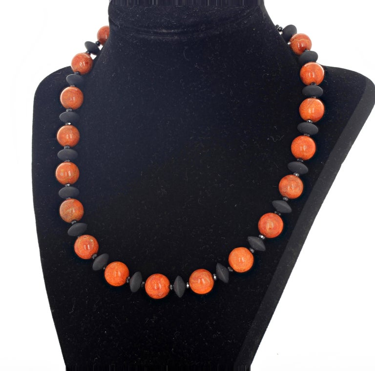 Rare round reddish orangy natural Bamboo Coral (11 mm) set with designer disks of beautiful polished flat black Onyx and brilliant gem cut sparkling little black Spinels in a necklace 18 inches long with a gold tone clasp.  More from this seller by
