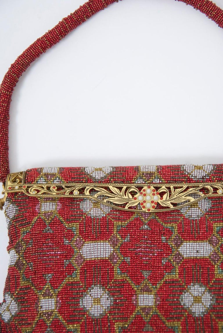 One of the most interesting designs I've seen of the high-style and beautifully crafted French beaded bags from the 1950s-'60s. This example has a red background, white quatrefoil designs and gold design outlines. Goldtone pierced frame, red beaded