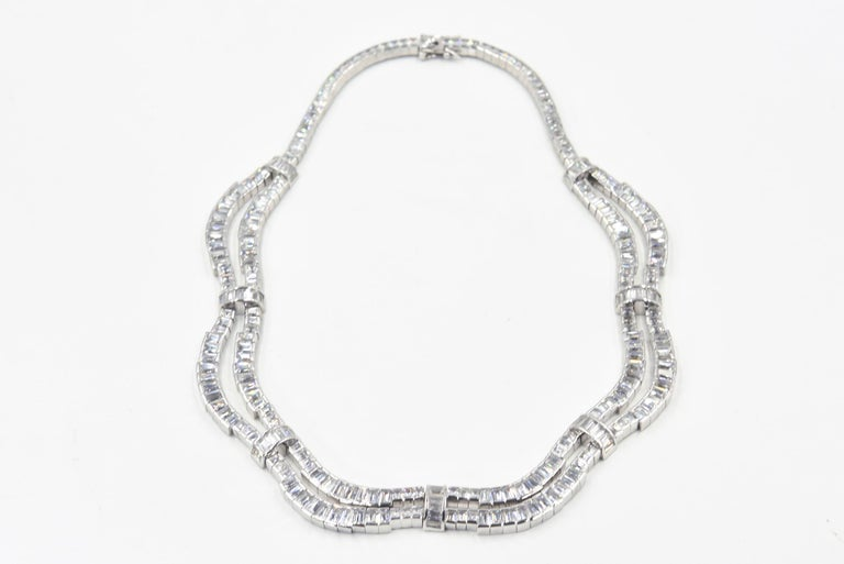 Elegant emerald cut cubic zirconia two row drop necklace with baguette CZ bridges set in rhodium sterling silver.  Perfect for a wedding, gala or big event.  Marked 925 on clasp.  It has a push button clasp with two safety clasps.  Difficult to