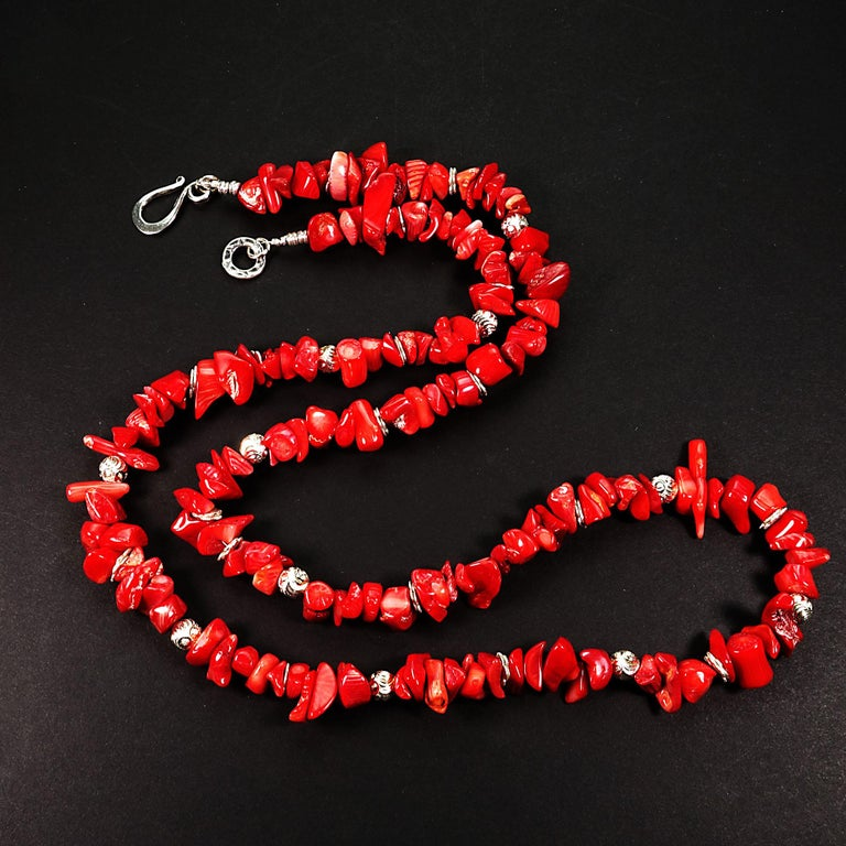 27.5 Inch necklace of Red Coral chips with silver toned accents.  These highly polished Red Coral chips are a lovely bright red and have all the natural beauty marks of coral.  This unique necklace is secured with a Sterling Silver hook and eye