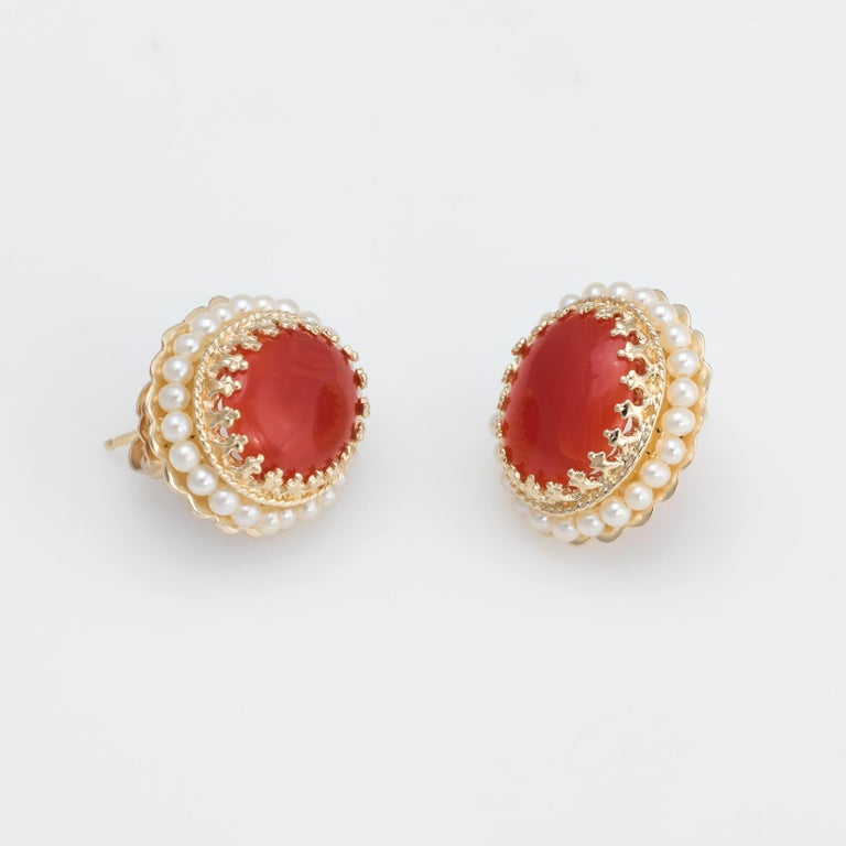 Elegant pair of estate red coral and seed pearl earrings, crafted in 14k yellow gold.   Cabochon cut red coral measures 12mm x 10mm (estimated at 5 carats each - 10 carats total estimated weight). The seed pearls measure (average) 2mm. The coral is