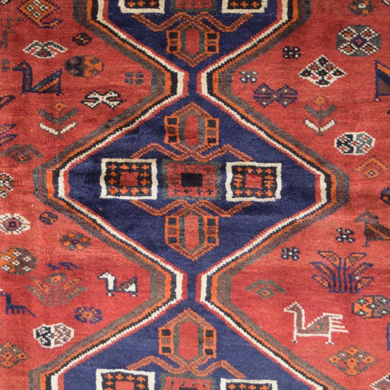"""Measuring 5'3"""" x 7'1"""", this Persian Ghashghai carpet in shades of red, blue, green, cream, and orange wool, is hand-knotted and belongs to Orley Shabahang's World Market Collection. To craft this carpet, the weaver utilized a Persian weaving"""