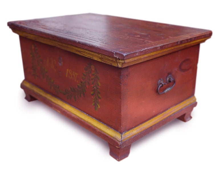 Italian (Tyrol) painted chest-box  Measures: H 25cm, W 46cm, D 31cm H 9.8 in, W 18.1 in, D 12.2 in     Fir-tree box painted in red. On the front there are floral motifs and the initials of the original owner and the date of construction,