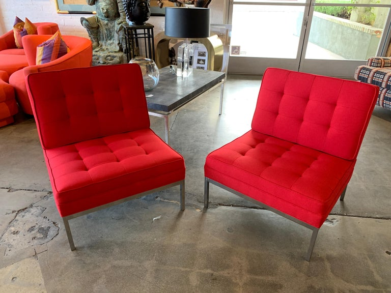 A pair of vintage Florence Knoll lounge chairs on steel bases. We have these totally refurbished and re-upholstered in red Maharam Messenger fabric. The bases have been polished, and the chairs look nice, with some minor marks to the bases.