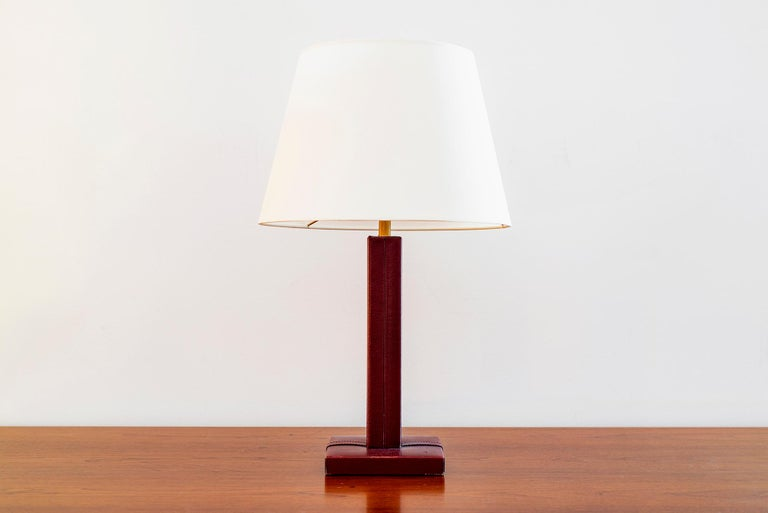 Jacques Adnet style table lamp. Aged red leather with signature contrast stitching.  New silk shade and newly rewired.