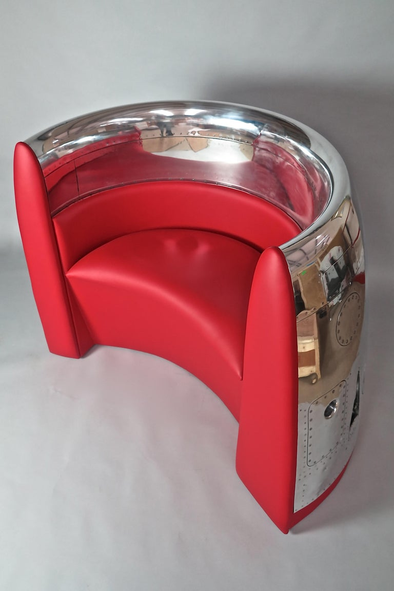 A highly polished jet cowling with a custom built premium leather red seat.  Many hours of skilled polishing, fine carpentry and upholstery creates a contemporary design seat for one or two persons.