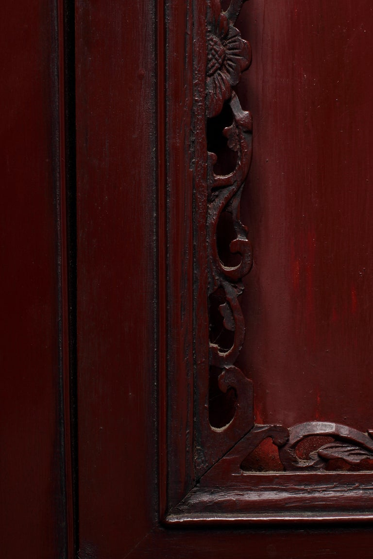 A 19th century Chinese red lacquer cabinet with drawers and doors. This Chinese red lacquer cabinet features multiple carved doors and drawers. The rectangular shape of this cabinet displays two pairs of doors below a row of three drawers and one