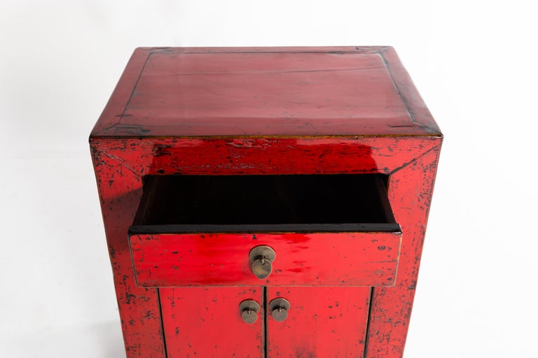 This red lacquer cabinet is from Shandong, China and was made from pine, elm, and lacquer, circa 1920. The piece features a pair of doors and a drawer for storage; wear consistent with age and use.