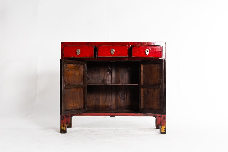 This cabinet is from Shandong, China and was made from elm, pine, and lacquer, circa 1920. The piece features 3 drawers, a pair of doors, red lacquer, and a shelf for storage. Wear consistent with age and use.
