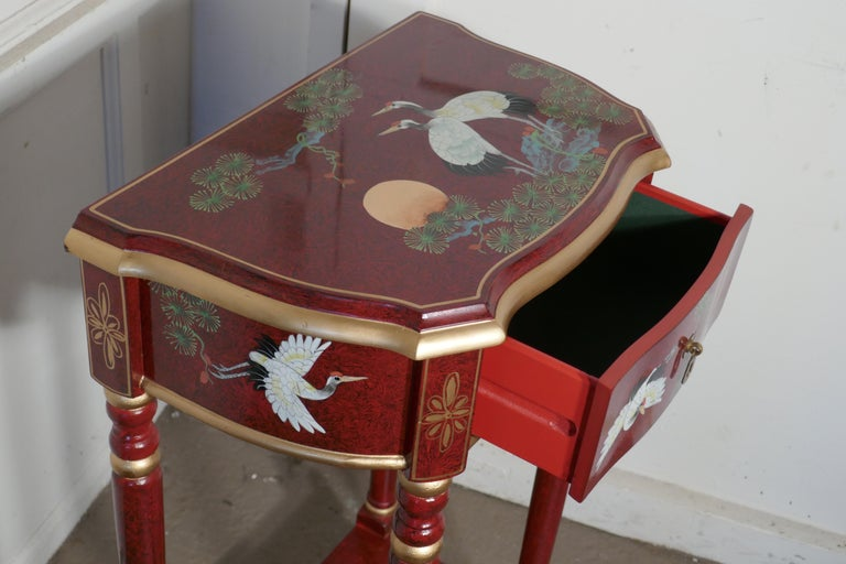Red Lacquer Chinoiserie Side Table  This is a very auspicious piece, the top of the table has a scene showing 2 Cranes (birds of life) and the Red Rising Sun It is a tall side table with an under tier and drawer decorated with japanned