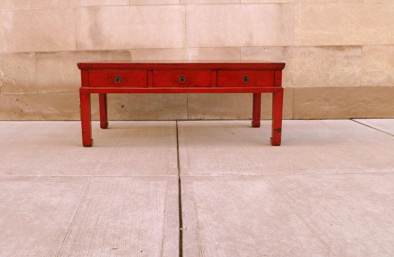 Antiques red lacquer low table with three drawers with brass pulls and straight legs with hoof feet.