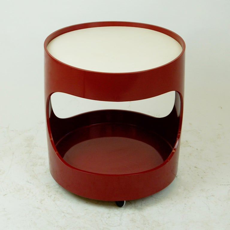 Charming red lacquered circular bar trolley or bar cart with a white top on wheels in very nice condition. The trolley is produced in Germany by Opal Kleinmöbel in the late 1960s and shows the original manufacturers mark on the underside. The German