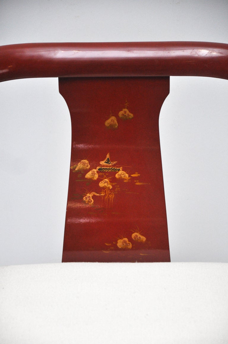 Chinoiserie style Chinese red lacquer horseshoe club chair. Chair has brass detailing. This Ming style chair has a hand painted scene on both the front and back. Seat height is 17