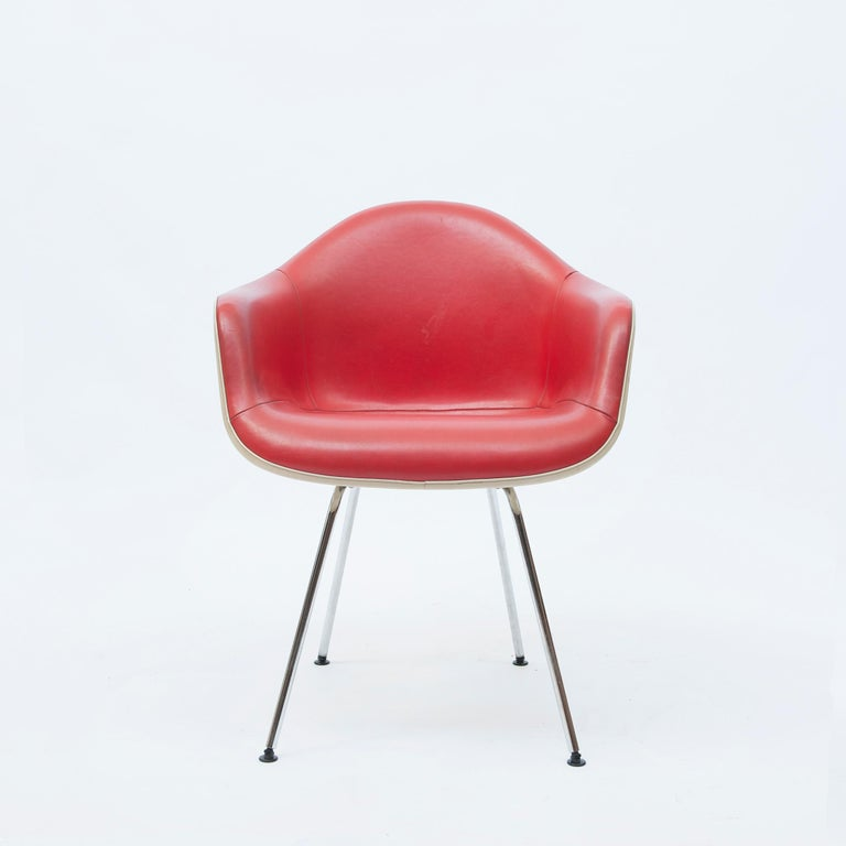 A Dax rope edge fiberglass Zenith shell chair designed by Charles & Ray Eames for Herman Miller Co. with aluminum-finished legs retaining the original red leather upholstery over a fiberglass shell.