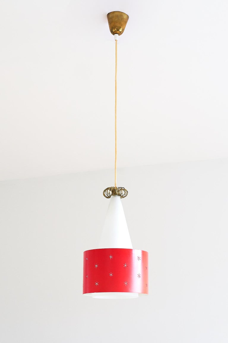 A rare red pendant designed by Paavo Tynell and produced by Idman in 1955. The model number is K2-10/ N-9241. The conical shade is made of a white matte glass, resulting in a soft and diffused light. The red painted metal ring appears to float