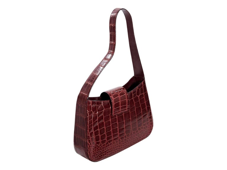 Product details:  Red alligator shoulder bag by Prada.  Single shoulder strap.  Top strap closure.  Lined interior with inner zip pocket.  Silvertone hardware.  Authenticity card included.  11