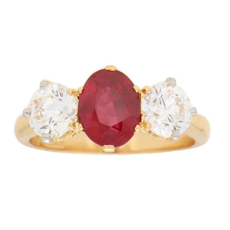 A beautiful vibrant red ruby and diamond trilogy engagement ring set in 18k yellow gold.  This classic design of engagement ring is centrally six-claw set with an oval cut ruby which is a beautiful vibrant red colour. This ruby is then sided by two