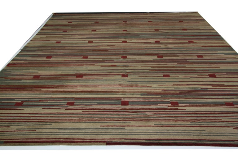 Red squares set against a background of beige, red and grey stripes makes for just the right amount of bold in a rug that can attract attention without detracting from other aspects of the space. Hand knotted in Nepal using wool dyed with natural