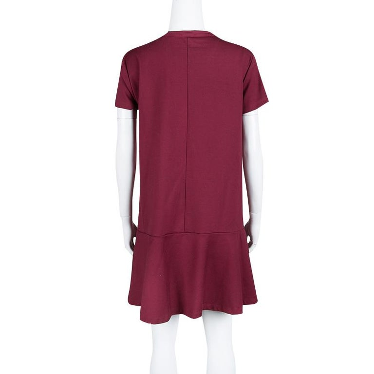 This shift dress from Red Valentino is amazing because it can be worn with flats or with high heels. The burgundy dress has comes designed with pleats on the front, short sleeves and a pelplum bottom.  Includes: The Luxury Closet Packaging